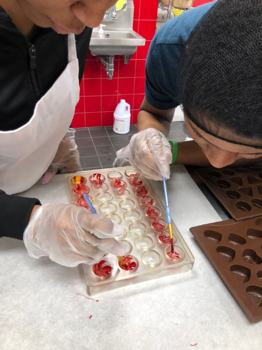 Students are decorating the chocolate.